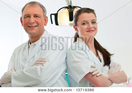 Dentists in their surgery looking at the viewer standing side by side