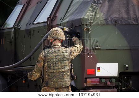 german soldier fuels a military armored truck