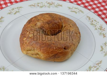 Whole maple flavored whole wheat bagel on white plate