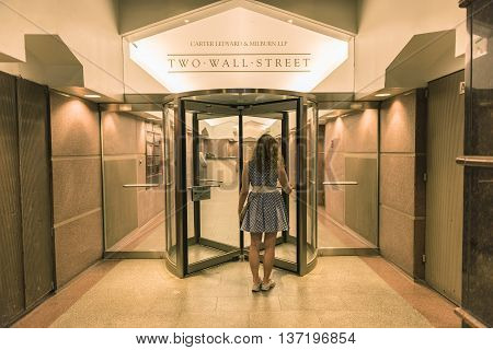 New York, USA - June 18, 2016: Young woman entering two wall street building from sidewalk with office of Carter Ledyard & Milburn LLP