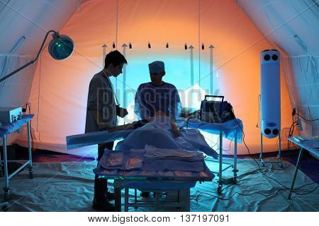 MOSCOW - APR 28, 2015: Medical worker and injured with a bandaged hand in the chamber module in a field hospital
