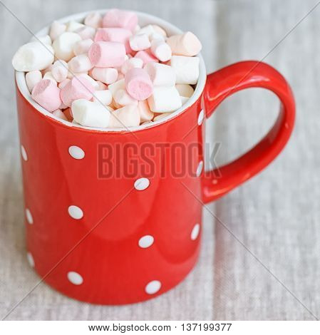 Red polka dot Cup filled marshmallow on gray fabric