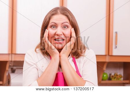 Frightened and worried woman wearing pink apron. Unhappy anxious and stressed housewife in kitchen. Negative facial emotion.