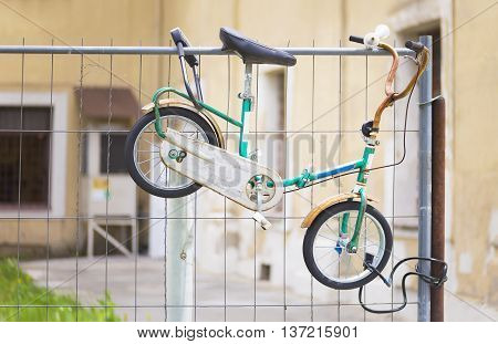 Child's old bicycle chained to a metal fence