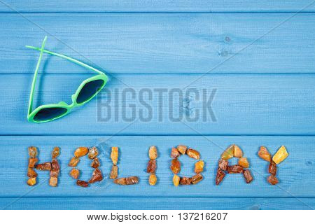 Word Holiday Made Of Amber Stones And Sunglasses On Blue Boards, Summer Time, Copy Space For Text