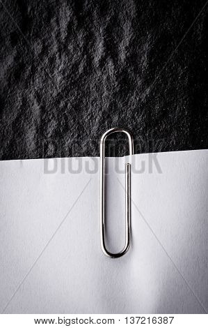 close up of a metal paper clip and paper on black background