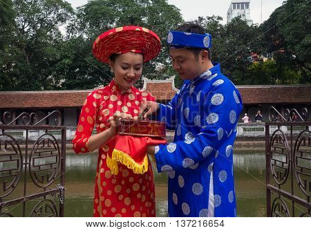 HA NOI, VIET NAM, April 30, 2016 the young couple, the wedding day, exchanged mementos, called betel nuts. At relics mieeud Quoc Tu Giam, Ha Noi, Vietnam