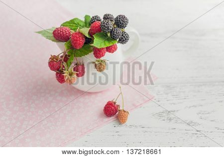 Raspberry bouquet in a saucer on wooden background