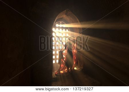 Novices are dressed with light shining through a window in the pagoda.