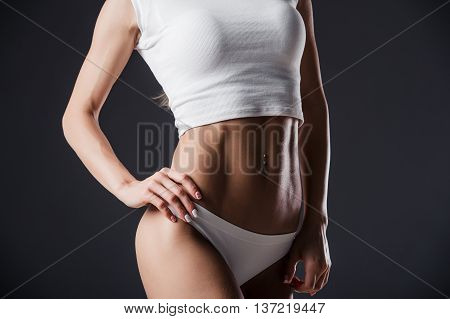 Close up of fit woman's torso with her hands on hips. Female with perfect abdomen muscles on black background.