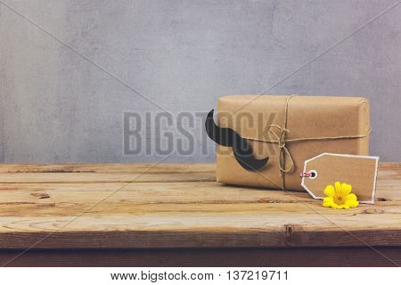 Gift box and gift tag on wooden table. Father's day holiday background.