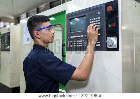 Man programming CNC machine in the factory