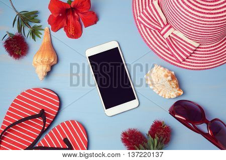 Smartphone mock up template with summer beach items and tropical flowers. View from above. Flat lay