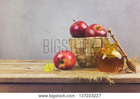 Apples nad honey jar on wooden table. Jewish holiday Rosh Hashanah background