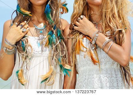 close up image of two hippie girls. boho style accessories