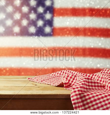 Empty wooden deck table with tablecloth over USA flag bokeh background. 4th of July celebration picnic background. Ready for product display montage.