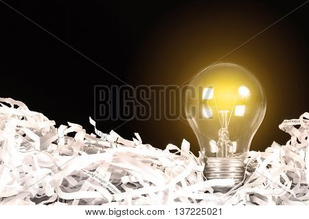 the yellow Light bulb glowing place on shredded recycled paper on black background idea innovation concept
