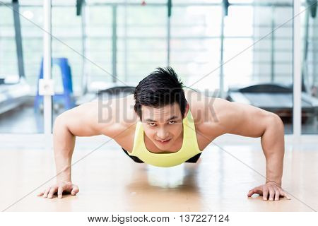Frontal view of muscular Asian man doing pushups in gym