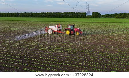 Tractor spraying field at spring, aerial view