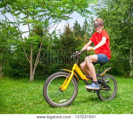 Cute teen boy wearing red tshirt and goggles riding a bicycle in a summer park looking at camera