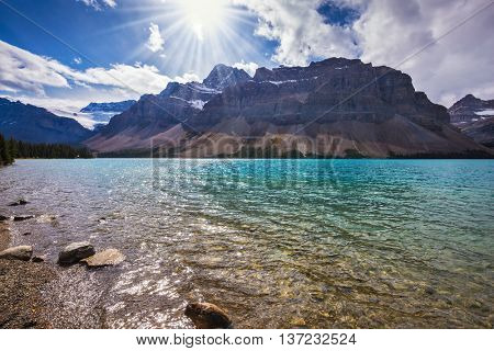 The cold waters of the lake surrounded by scenic Canadian Rocky Mountains. Azure Bow Lake in Banff National Park
