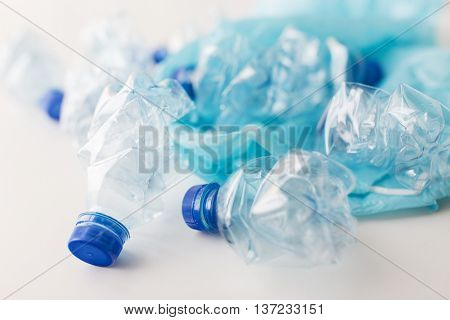 waste recycling, reuse, garbage disposal, environment and ecology concept - close up of empty used crashed plastic water bottles and rubbish bag on table