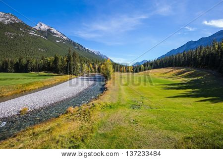 Sunny autumn day in the Rocky Mountains of Canada. The drying-up stream among the woods and mountains of park Banff