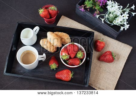Coffee mini French pastries and strawberries on wooden tray over black table. White and purple flowers in a decorative wooden crate. Black background