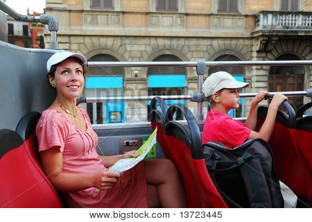 young mother and little son looking on street of Rome in tour bus in Rome, Italy, focus on mother