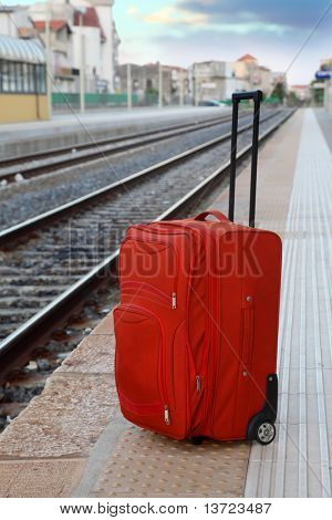 big red travel bag stands on platform near railway tracks. perspective