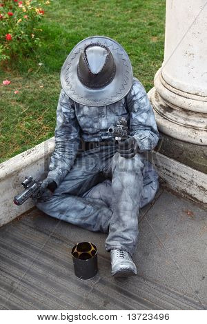 alive sculpture of cowboy sitting, ask for handout and keep revolvers