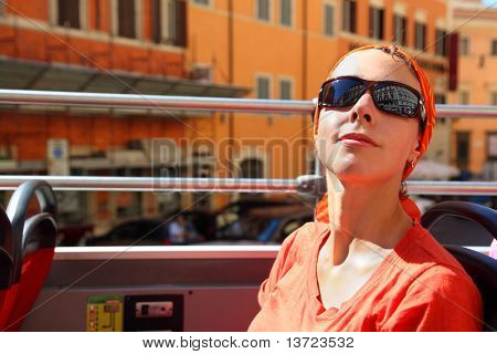 beautiful young woman looking on street of Rome in tour bus in Rome, Italy