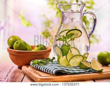 Country drink. On wooden boards is glass jug with transparent drink and lime glue bowl. A drink number thirty one with ice cubes . Country life. Light background.