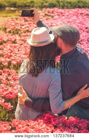 Happy loving tourists taking selfie photos in a tulip field, focus on the cell phone