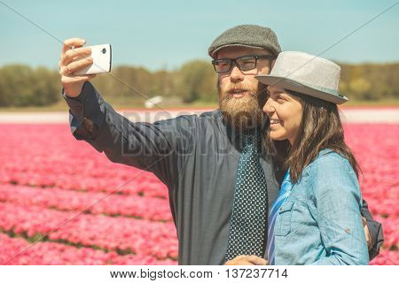 Happy loving tourists taking selfie photos in a tulip field