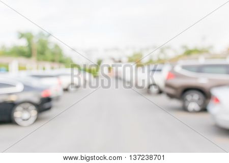Blurred abstract photo of outdoor car park in countryside background.