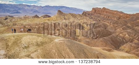 DEATH VALLEY, USA - OCTOBER 15, 2015: People posing in front of Zabriskie point in Death Valley National Park
