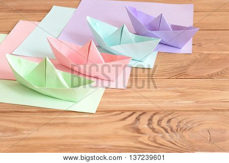 Four colored origami boats toys on a wooden table. Square sheets of colored paper. Creative paper crafts idea for summer vacation. DIY origami project for kids