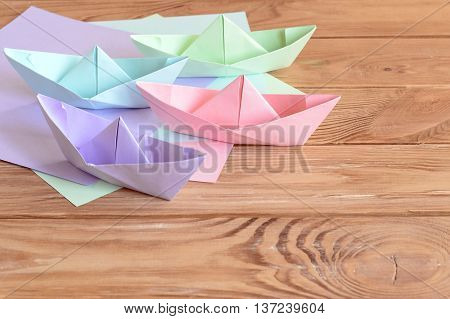Pink, green, blue, lilac paper boats toys on wooden background. Sheets of colored paper. Idea for childrens origami crafts in kindergarten, summer camp, at home