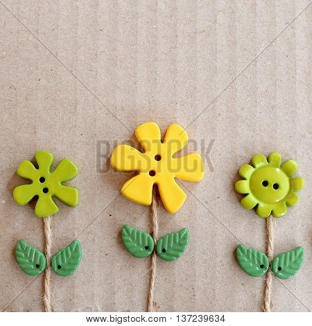 Cardboard background with green and yellow plastic buttons flowers and leaves. Summer fun background with empty copy space for text