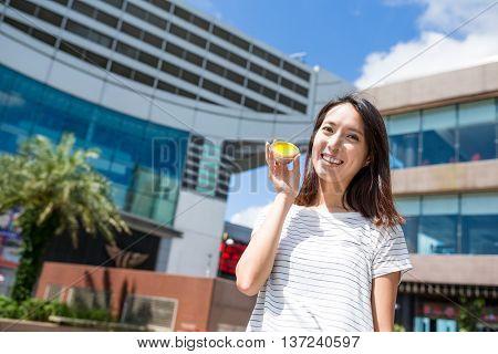 Woman holding famous Hong Kong local food, egg tart