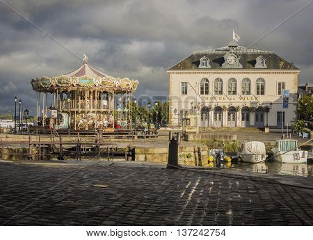 HONFLEUR HARBOUR, HONFLEUR, NORMANDY, FRANCE, 9 SEPTEMBER 2013 - Honfleur town hall and carousel in the eveing sunshine Honfleur France