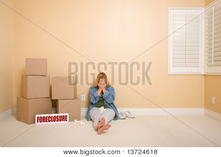 Upset Woman with Tissues on Floor Next to Boxes and Foreclosure Real Estate Sign in Empty Room.