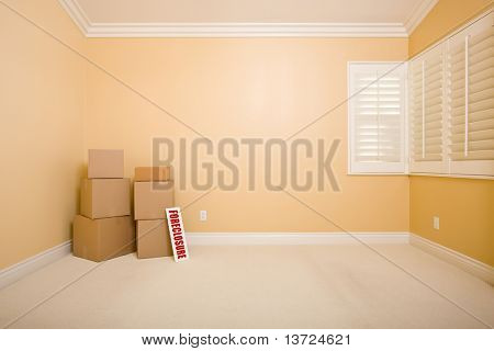 Moving Boxes and Foreclosure Real Estate Sign on Floor in Empty Room with Copy Space on Blank Wall.