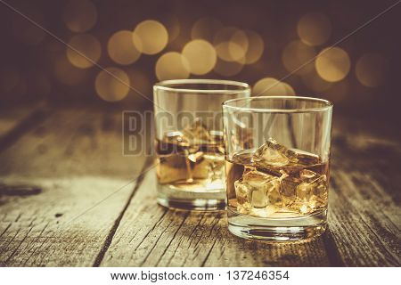 Cognac in glasses on rustic background with bokeh at background, toned