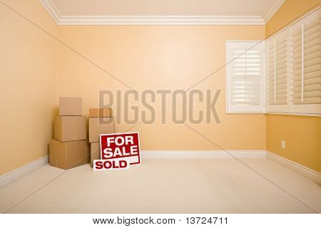 Moving Boxes, For Sale and Sold Real Estate Signs on Floor in Empty Room with Copy Space on Blank Wall.