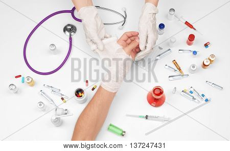 Close-up female doctor is bandaging hand of patient on white background
