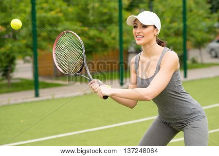 Skillful sportswoman is playing tennis. She is standing and preparing to return the ball. Girl is smiling