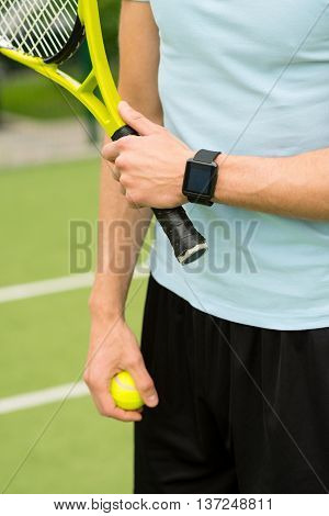 Close up of male arms holding tennis ball and racquet. Man is standing in stadium. Focus on smart watch on his wrist