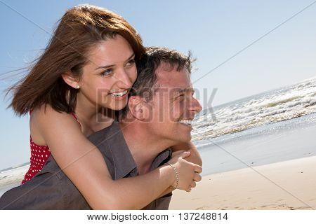 Love - Happy Couple On Beach Having Fun Piggyback Ride